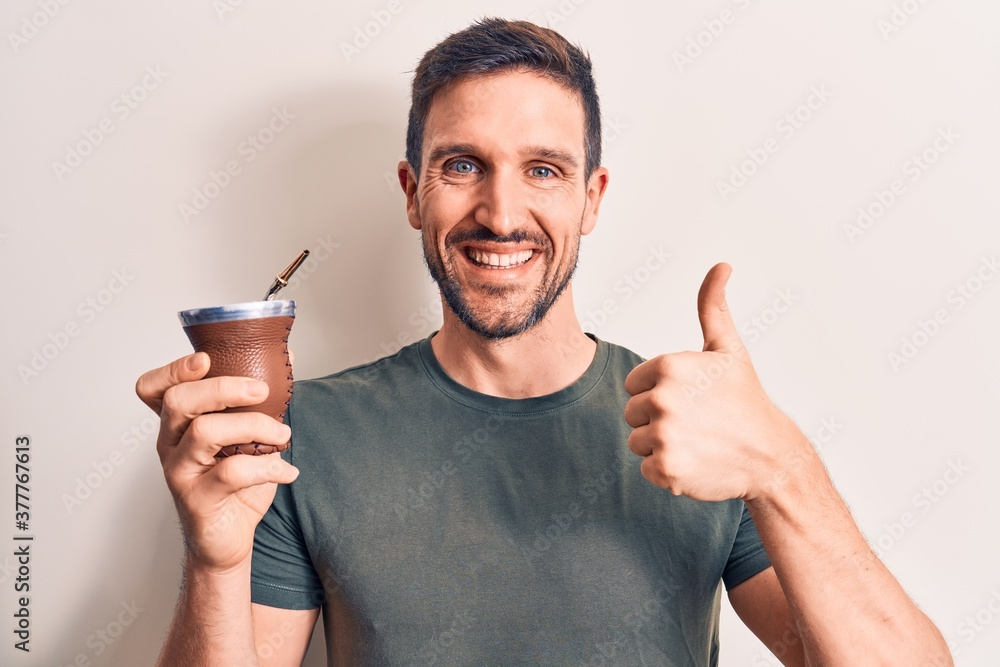 Fototapeta Young handsome man drinking mate infusion beverage over isolated white background smiling happy and positive, thumb up doing excellent and approval sign