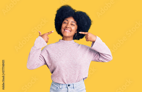 Fotografija Young african american girl wearing casual clothes smiling cheerful showing and pointing with fingers teeth and mouth