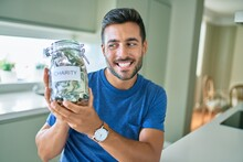 Young Handsome Man Smiling Happy Holding Charity Jar With Money At Home