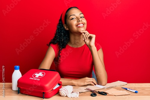 Fotografie, Tablou Young african american girl sitting on the table with first aid kit making cure smiling looking confident at the camera with crossed arms and hand on chin