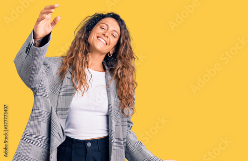 Fototapeta Young hispanic woman with tattoo wearing business oversize jacket looking at the camera smiling with open arms for hug