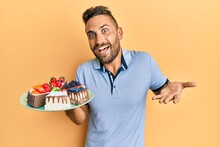 Handsome Man With Beard Holding Cake Slices Celebrating Achievement With Happy Smile And Winner Expression With Raised Hand