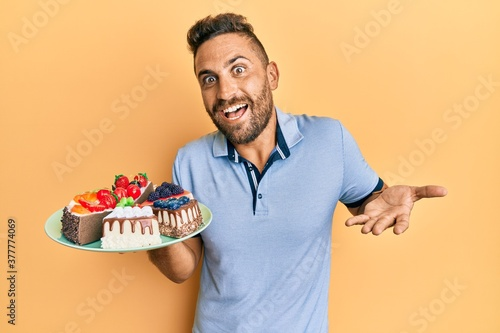 Fototapeta Handsome man with beard holding cake slices celebrating achievement with happy smile and winner expression with raised hand obraz