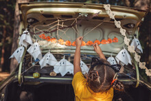 Safe Distant Halloween Celebration. Kids Preparing Decoration For Party In The Trunk Of Car