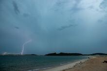 Lightning Striking Ground Near The Beach Shoreline.