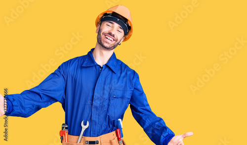 Fototapeta Young hispanic man wearing worker uniform looking at the camera smiling with open arms for hug