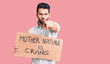 canvas print picture Young handsome man with beard holding mother nature is crying cardboard banner pointing with finger to the camera and to you, confident gesture looking serious