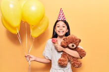 Adorable Hispanic Child Girl Wearing Birthday Hat Smiling Happy. Standing With Smile On Face Holding Balloons And Teddy Bear Eating Ice Cream Over Isolated Yellow Background