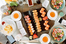 Top View Of Table Full Of Asian Food, Sushi, Tuna And Vegetable Salads, White Porcelain Tea Cups And Table Items, Selective Focus