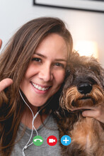 Happy Woman Having A Zoom Video Call Meeting With Her Dog While Waving At The Camera - Focus On Girl Face