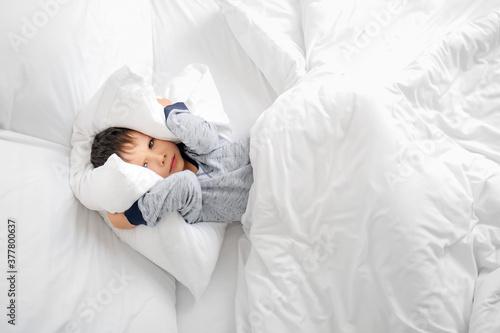 Fotografía Little boy suffering from sleep disorder in bedroom