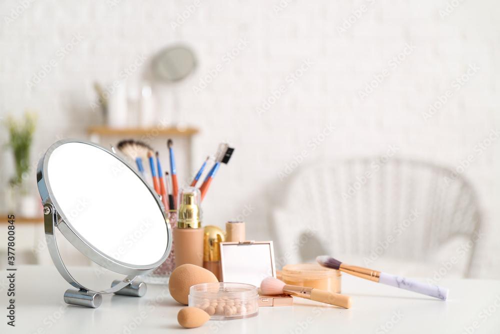Fototapeta Set of decorative cosmetics and mirror on dressing table