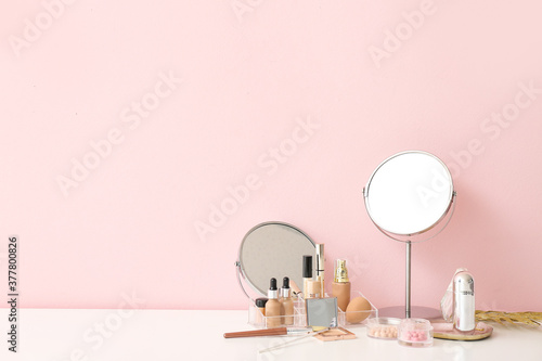 Photo Set of decorative cosmetics and mirrors on dressing table