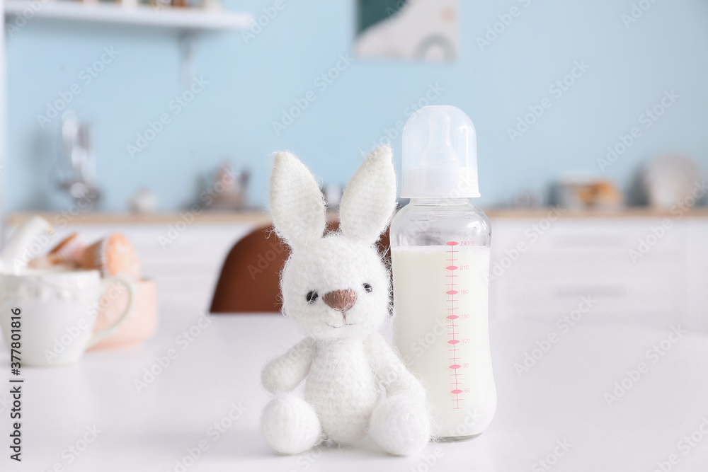 Fototapeta Bottle of milk for baby with toy on table in kitchen