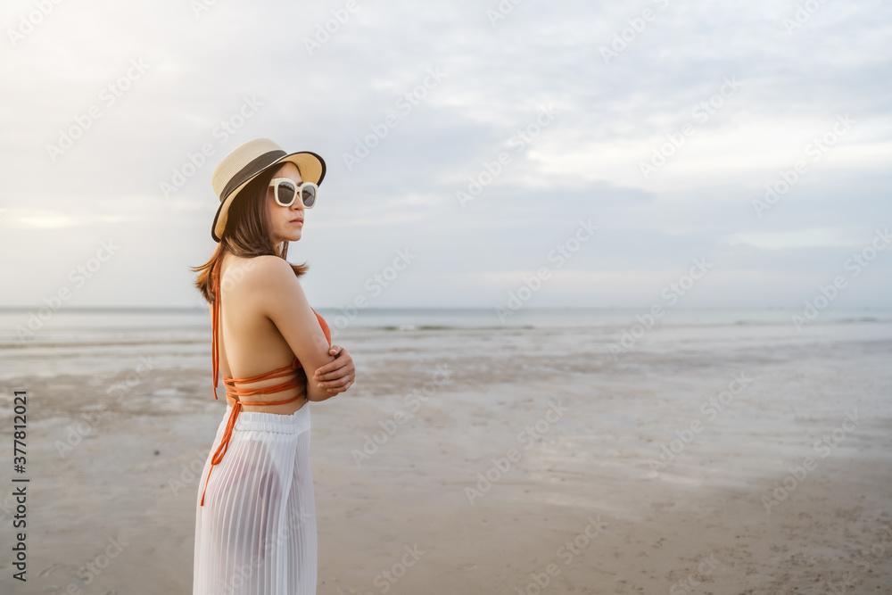 Fototapeta woman in bikini standing with arms crossed on sea beach