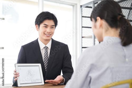 Fototapeta タブレットを使って部屋の説明をする日本人男性不動産営業職 obraz