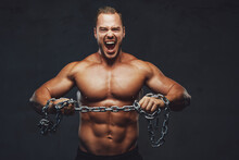 Musculate Guy With Naked Torso Trying To Break The Chain And Cry In Grung Background.