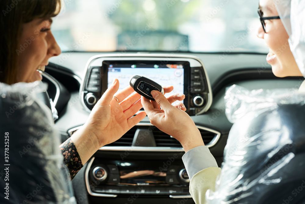 Fototapeta Happy woman getting a key from her new car giving by salesman while they sitting in salon of a new car