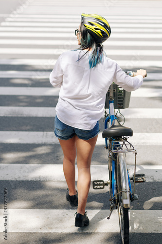 Fotografija Young woman in white shirt and denim shorts walking next to bicycle when crossin