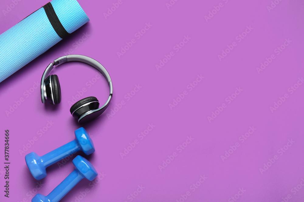 Fototapeta Yoga mat, dumbbells and headphones on color background