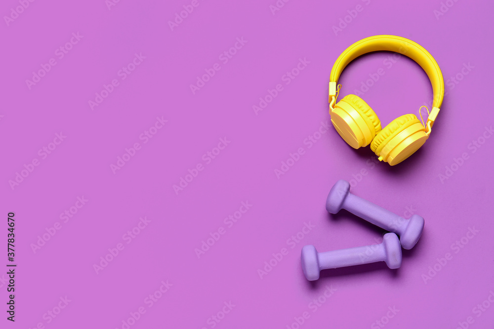 Fototapeta Dumbbells and headphones on color background