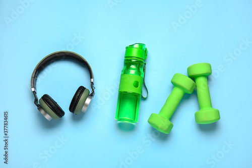 Bottle of water, dumbbells and headphones on color background