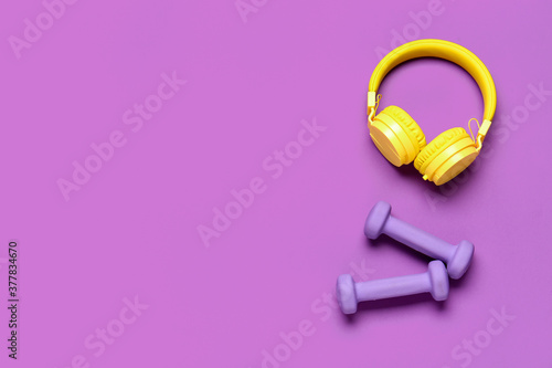 Dumbbells and headphones on color background