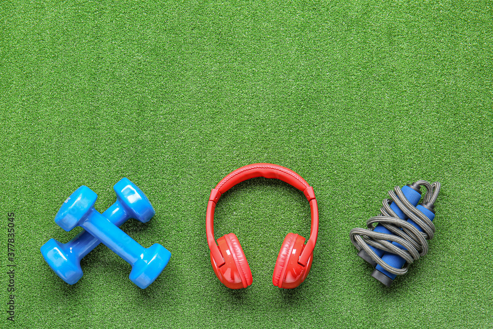 Fototapeta Dumbbells, jumping rope and headphones on color background