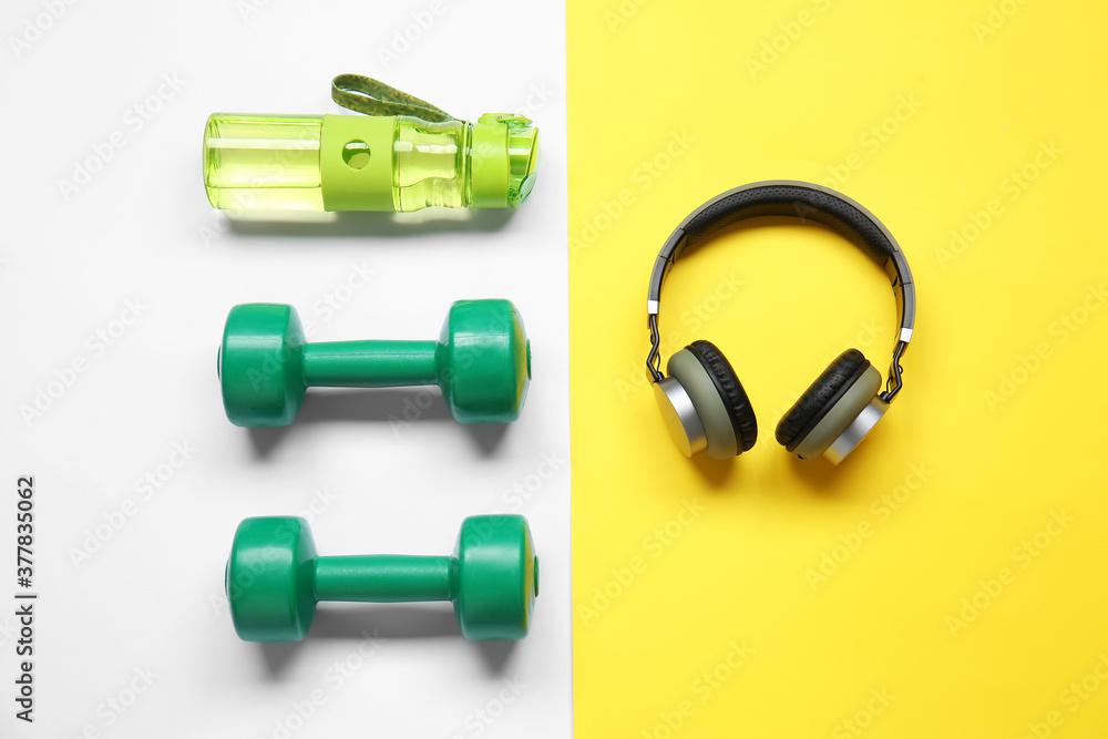 Fototapeta Bottle of water, dumbbells and headphones on color background