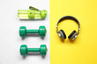 canvas print picture - Bottle of water, dumbbells and headphones on color background