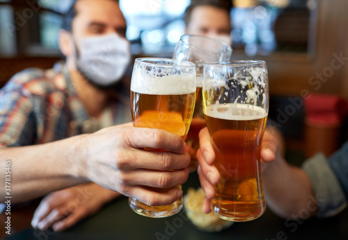 Obraz people, leisure and pandemic concept - male friends wearing face protective medical masks for protection from virus disease drinking beer and clinking glasses at bar or pub - fototapety do salonu