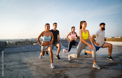 Group of cheerful fit fitness team exercising together outdoor Fototapeta