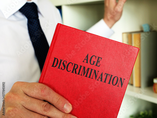 Fototapeta A lawyer shows an Age discrimination law book in the office. obraz