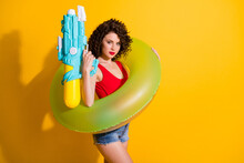 Photo Of Charming Cute Young Lady Hold Water Gun Swim Ring Calm Wait Her Company Play Beach Wear Jeans Shorts Red Singlet Unclothed Shoulders Isolated Vivid Yellow Color Background