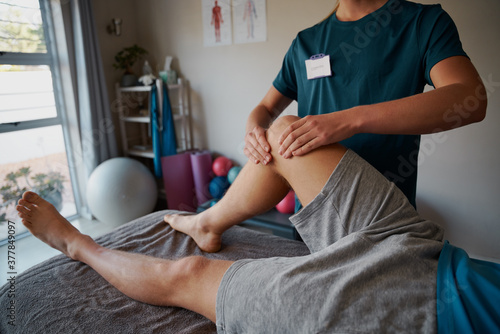 Foto Closeup of young female physiotherapist hands giving leg exercise to patient in