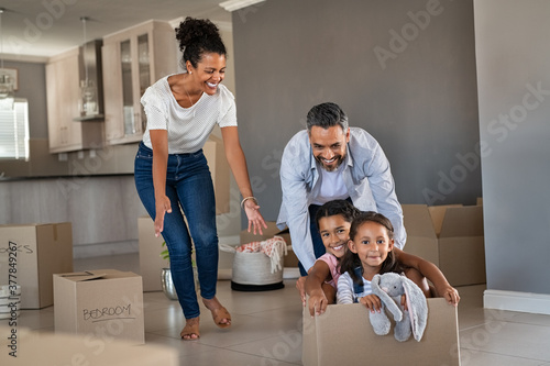 Obraz Parents playing with children while moving into new home - fototapety do salonu