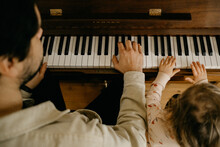 Father And Child Playing Piano Together