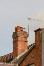 Red Brick Chimney Stack With Clay Pots And TV Aerial On English Tiled Rooftop