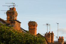 Red Brick Chimney Stacks And TV Aerials On English Terrace Rooftop Against Blue Sky