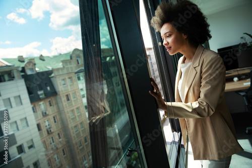 Fototapeta Beautiful african business woman looking outside window in office
