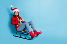 Photo Portrait Of Woman Riding Sleigh Into Blank Space Isolated On Pastel Light Blue Colored Background