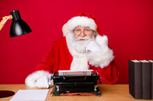 Photo Of Santa Claus Grey Beard Sit Desk Fist Cheek Vintage Typewriter Lamp Paper Book Wear X-mas Costume Coat Cap Glasses Isolated Red Color Background