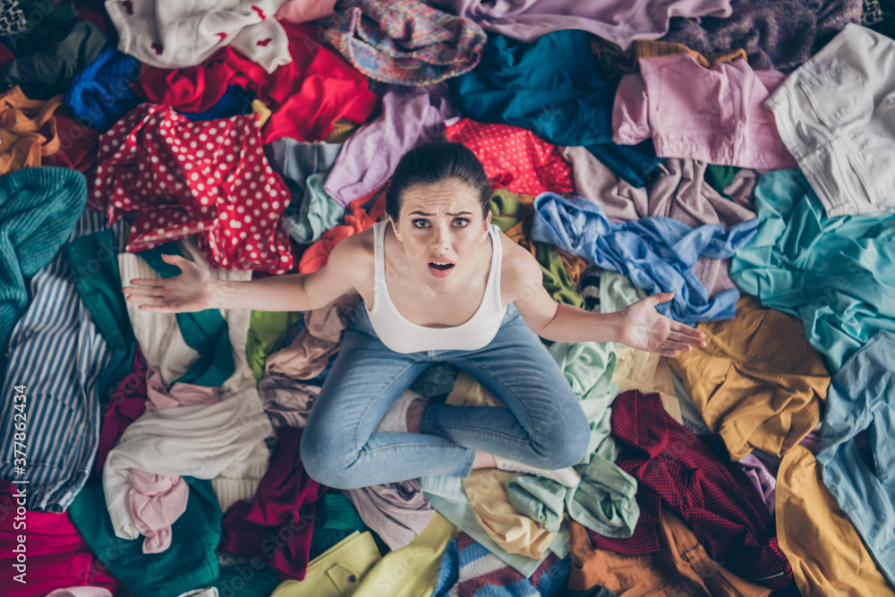 Fototapeta High angle above view photo of stressed helpless lady stay home spring cleaning household sit many clothes stack floor pick select outfit nothing to wear concept all stuff dirty indoors