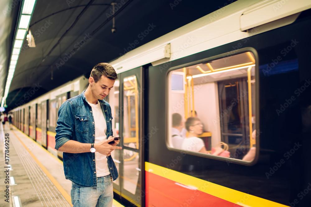 Fototapeta Thoughtful man surfing mobile phone in underground