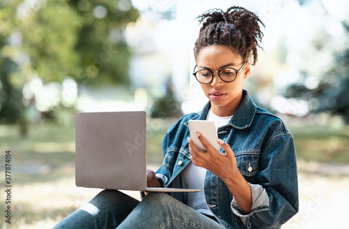 Girl Frowning Holding Phone Reading Message Sitting With Laptop Outside Wallpaper Mural