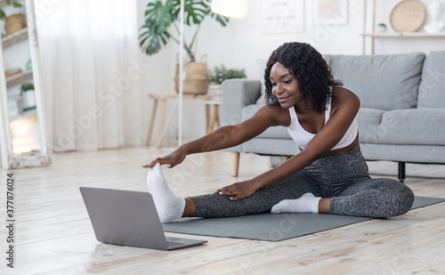 Fototapeta Slim black girl making morning exercise at home obraz