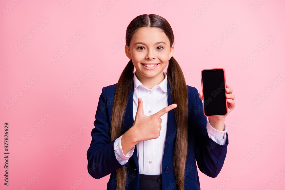 Fototapeta Portrait of her she nice attractive pretty cheerful cheery small little girl demonstrating device gadget display advert offer cellular isolated over pink pastel color background