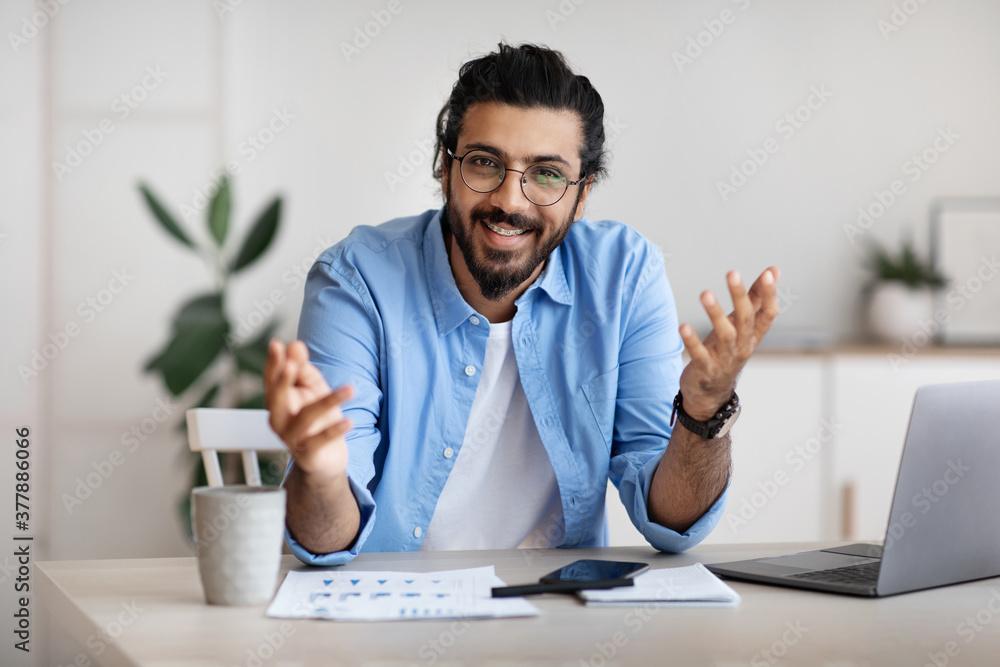 Fototapeta Young indian freelancer guy sitting at desk in office, talking at camera