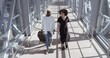 African woman and American black man walk together talking, carry suitcases, enter airport terminal or train station, meet two passengers before boarding, travel vacation together friends or marrieds