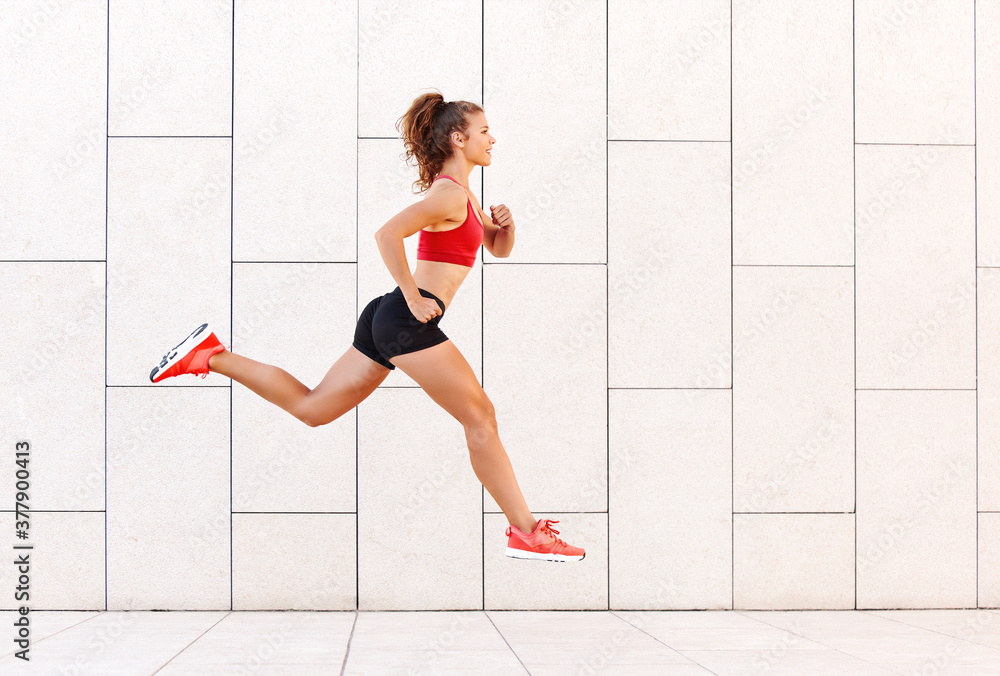 Fototapeta Concept of sporting success. strong girl runs and jumps high against the background of the city wall.